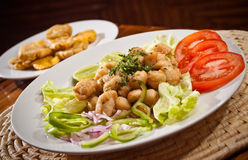 Delicious breaded calamari served with plantain Royalty Free Stock Image