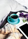 Delicious breakfast in bed with flowers. Croissant with coffee and a tablet for rest Stock Photos