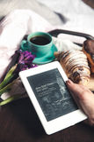 Delicious breakfast in bed with flowers. Croissant with coffee and a tablet for rest Stock Images