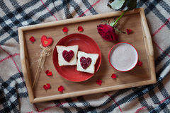 Delicious breakfast in bed on valentines day. Celebration holiday romantic present with rose flower, toasts and hot chocolate. Top view Stock Image
