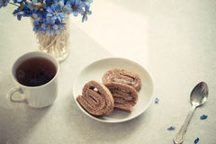 Delicious breakfast - biscuit roll with black tea on a background of sunny violets. Delicious breakfast - biscuit roll with tea on a background of sunny violets Stock Images