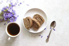 Delicious breakfast - biscuit roll with black tea on a background of sunny violets.  Royalty Free Stock Image