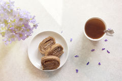 Delicious breakfast - biscuit roll with tea on a background of sunny violets.  Stock Image