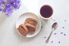 Delicious breakfast - biscuit roll with tea on a background of sunny violets.  Royalty Free Stock Photography
