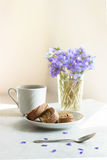 Delicious breakfast - biscuit roll with tea on a background of sunny violets.  Stock Photography