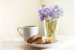 Delicious breakfast - biscuit roll with tea on a background of sunny violets.  Stock Photo