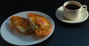 Delicious breakfast. Black coffee, avocado sandwiches, egg and cheese on a dark background. royalty free stock images