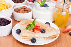 Delicious breakfast - crepes with fresh berries and honey stock photography