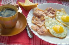 Delicious Breakfast - a Cup of coffee, a plate of fried eggs, bacon and toast, next to the Cutlery on red checkered napkin.  Royalty Free Stock Photo