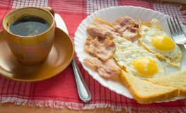 Delicious Breakfast - a Cup of coffee, a plate of fried eggs, bacon and toast, next to the Cutlery on red checkered napkin.  Stock Photo
