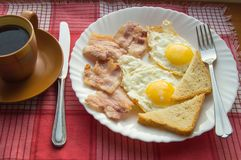Delicious Breakfast - a Cup of coffee, a plate of fried eggs, bacon and toast, next to the Cutlery on red checkered napkin.  Royalty Free Stock Photos