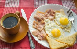 Delicious Breakfast - a Cup of coffee, a plate of fried eggs, bacon and toast, next to the Cutlery on red checkered napkin.  Stock Photography