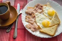 Delicious Breakfast - a Cup of coffee, a plate of fried eggs, bacon and toast, next to the Cutlery on red checkered napkin.  Stock Image