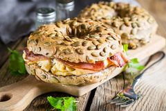 Breakfast bagel with omelet and bacon. Delicious breakfast, egg and bacon bagel royalty free stock photo