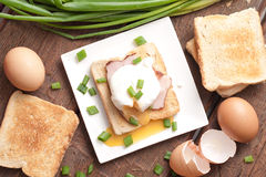 Delicious breakfast. Eggs benedict with ham on toast. Stock Photos