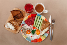 Delicious Breakfast from Eggs,Bread with Butter,Sausage on the Colorfull Plate.Coffee,Red Juice  with White Flowers.Knife and Folk Stock Images
