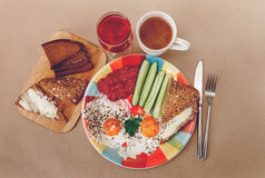 Delicious Breakfast from Eggs,Bread with Butter,Sausage on the Colorfull Plate.Coffee,Red Juice  with White Flowers.Knife and Folk Stock Photo