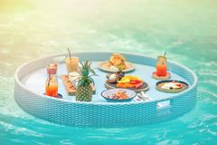 Delicious Breakfast on the floating table in the pool.tint. illumination.  royalty free stock image