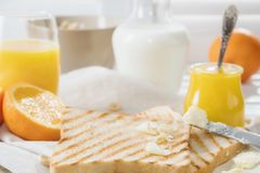 Delicious breakfast, french toasts with butter and honey,. Fresh oranges and juice Stock Photos