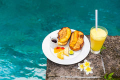 Delicious breakfast with french toasts with fried banana, honey. And fresh fruit on a plate on old stone tiles. Pool in the background Royalty Free Stock Photo