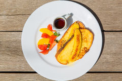 Delicious breakfast with french toasts with fried banana, honey. And fresh fruit on a plate on old wooden background Royalty Free Stock Photos