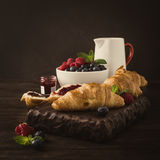 Delicious breakfast with fresh croissants. Retro style toned photo of delicious breakfast with fresh croissants and ripe berries on old wooden background Royalty Free Stock Image