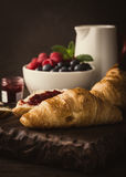 Delicious breakfast with fresh croissants. Retro style toned photo of delicious breakfast with fresh croissants and ripe berries on old wooden background Royalty Free Stock Photos