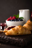 Delicious breakfast with fresh croissants. Fresh croissants and ripe berries on old wooden background. Healthy breakfast concept with copy space. Dark photo Royalty Free Stock Photos