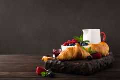 Delicious breakfast with fresh croissants. Fresh croissants and ripe berries on old wooden background. Healthy breakfast concept with copy space. Dark photo Royalty Free Stock Images