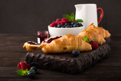Delicious breakfast with fresh croissants. Fresh croissants and ripe berries on old wooden background. Healthy breakfast concept with copy space. Dark photo Stock Photography
