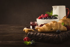 Delicious breakfast with fresh croissants. Fresh croissants and ripe berries on old wooden background. Healthy breakfast concept with copy space. Retro style Stock Photography