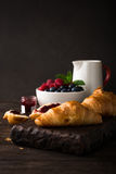 Delicious breakfast with fresh croissants. And ripe berries on old wooden background. Healthy food concept with copy space. Dark photo Stock Photos