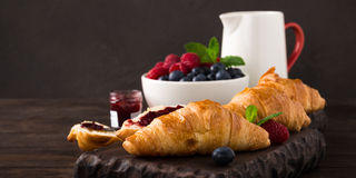Delicious breakfast with fresh croissants. And ripe berries on old wooden background. Healthy food concept with copy space. Dark photo Royalty Free Stock Photos