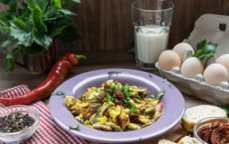 Scrambled egg with dried tomatoes and home baked goods stock photography