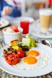 Breakfast with fried eggs. Delicious breakfast with fried eggs, bacon and vegetables Royalty Free Stock Photos