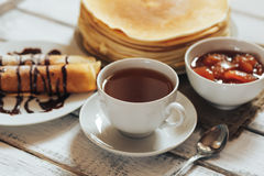 Delicious breakfast. Homemade Pancakes or blini with chocolate cream and cup. Of black tea on white wooden rustic background table, close-up. Vintage style royalty free stock images
