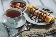 Delicious breakfast. Homemade Pancakes or blini with chocolate cream and cup. Of black tea on white wooden rustic background table, close-up. Vintage style royalty free stock photography