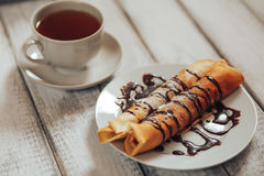 Delicious breakfast. Homemade Pancakes or blini with chocolate cream and cup. Of black tea on white wooden rustic background table, close-up royalty free stock photo