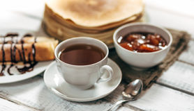 Delicious breakfast. Homemade Pancakes or blini with chocolate cream and cup. Of black tea on white wooden rustic background table, close-up. Vintage style stock images