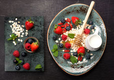Delicious breakfast oatmeal, fresh  berries, honey and milk. top view Stock Photos