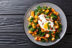 Delicious Breakfast Of Sweet Potato With Kale, Bacon And Fried Egg Close-up On A Plate. Horizontal Top View Royalty Free Stock Image