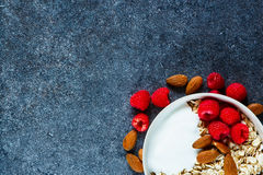 Delicious breakfast over stone. Bowl with cereal, nuts and fresh raspberry for delicious breakfast on stone texture. Dark background layout with free text space Royalty Free Stock Images