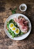 Delicious breakfast, snack, appetizers - sandwiches with prosciutto, egg, arugula and cream cheese on a dark background stock image