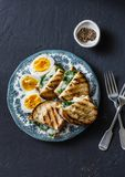 Delicious breakfast or snack - boiled eggs, spinach, grilled cheese sandwiches on dark background Stock Images