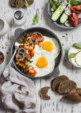 Delicious  breakfast or snack - a fried egg, beans in tomato sauce with onions and carrots, fresh cucumbers and tomatoes, homemade Royalty Free Stock Image