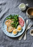 Delicious breakfast or snack - salami sausage, boiled egg, arugula, grilled bread and coffee on a gray background stock photography