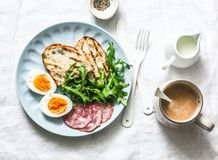 Delicious breakfast or snack - salami sausage, boiled egg, arugula, grilled bread and coffee on a light background. Top view royalty free stock photos