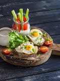 Delicious breakfast or snack -  sandwich with cheese and a fried quail egg, greek yogurt, celery and sweet peppers on rustic woode Royalty Free Stock Images
