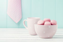 Delicious breakfast. Some macarons (macaroons) in a bowl and a pink polka dots mug on a white wooden table. Vintage scene Royalty Free Stock Images