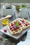 Delicious breakfast with waffles and raspberries. Delicious breakfast with waffles, fresh raspberries and coffee Royalty Free Stock Image